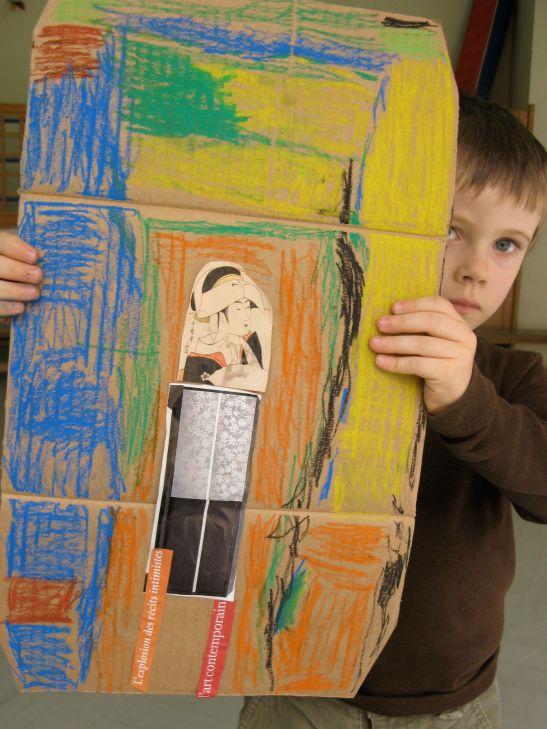 L'oeuvre d'un enfant en maternelle apres l'exercice de realisation de portraits utilisant papiers decoupes et pastels sur cartons. Esprit Street Art.